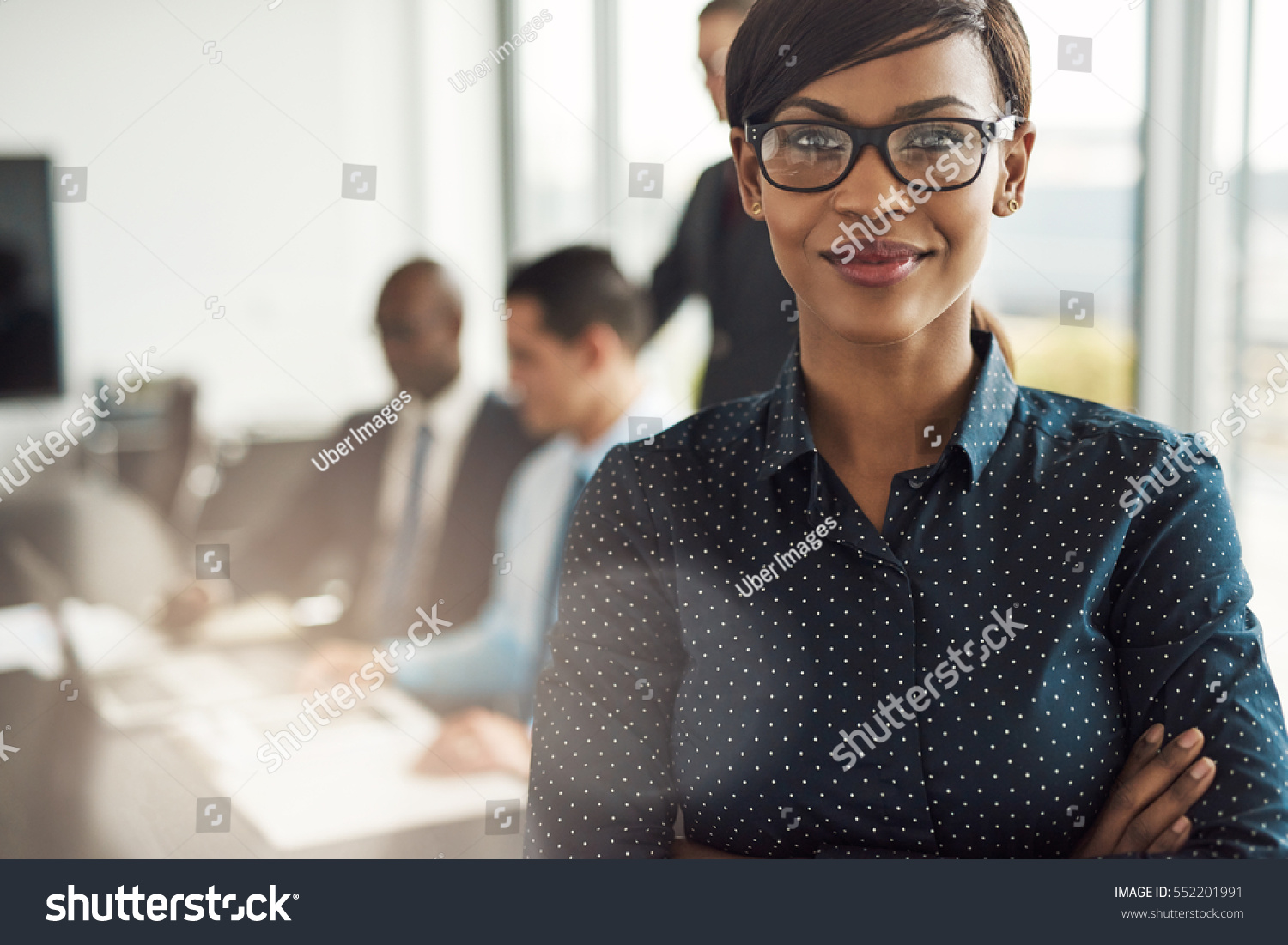 stock-photo-beautiful-young-grinning-professional-black-woman-in-office-with-eyeglasses-folded-arms-and-552201991.jpg
